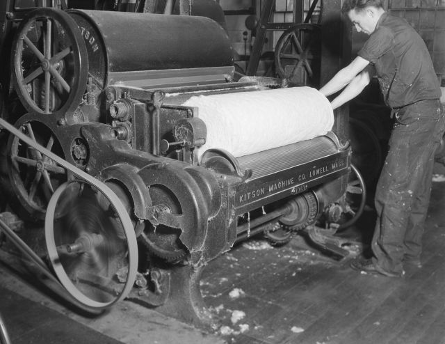 Textile Manufacturing: man rolling fabric.