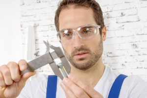 a young man measuring screw using caliper