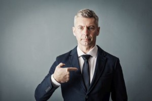 Businessman is pointing at himself