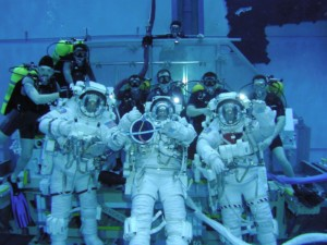 Szkolenie astronautów NASA - JSC2005-E-14733 (21 March 2005) —Three STS-114 astronauts give a simultaneous thumbs-up signal to indicate preparedness during an underwater training session in the Neutral Buoyancy Laboratory in Houston. From the left are Soichi Noguchi of JAXA, Stephen K. Robinson and Andrew S.W. Thomas. A number of SCUBA-equipped divers participated in the dive to assist the astronauts. Noguchi and Robinson have been in training for a lengthy period of time, preparing for three scheduled spacewalks on the first flight marking return to space following the Columbia mission of 2003. Thomas, working inside the Space Shuttle Discovery's cabin, will serve as the lead robotics officer for the inspection of the Orbiter's thermal protection system using a new boom extension outfitted with sensors and cameras. He will also serve as the Intravehicular Activity crewmember helping to suit up and choreograph spacewalkers Noguchi and Robinson for their spacewalks. Image by NASA and in public domain. Thanks, NASA!