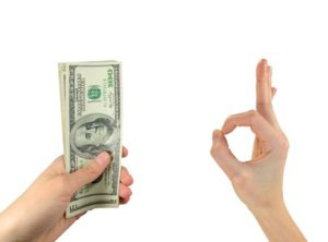 Business and finance concept. Image of dollars in the man's hand, the other hand shows gesture ok. Isolated on white background